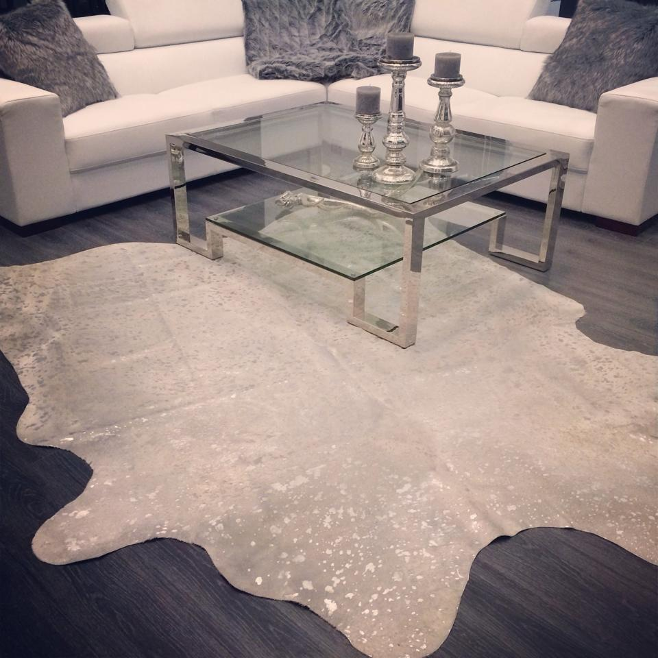 Cowhide rug under glass coffee table