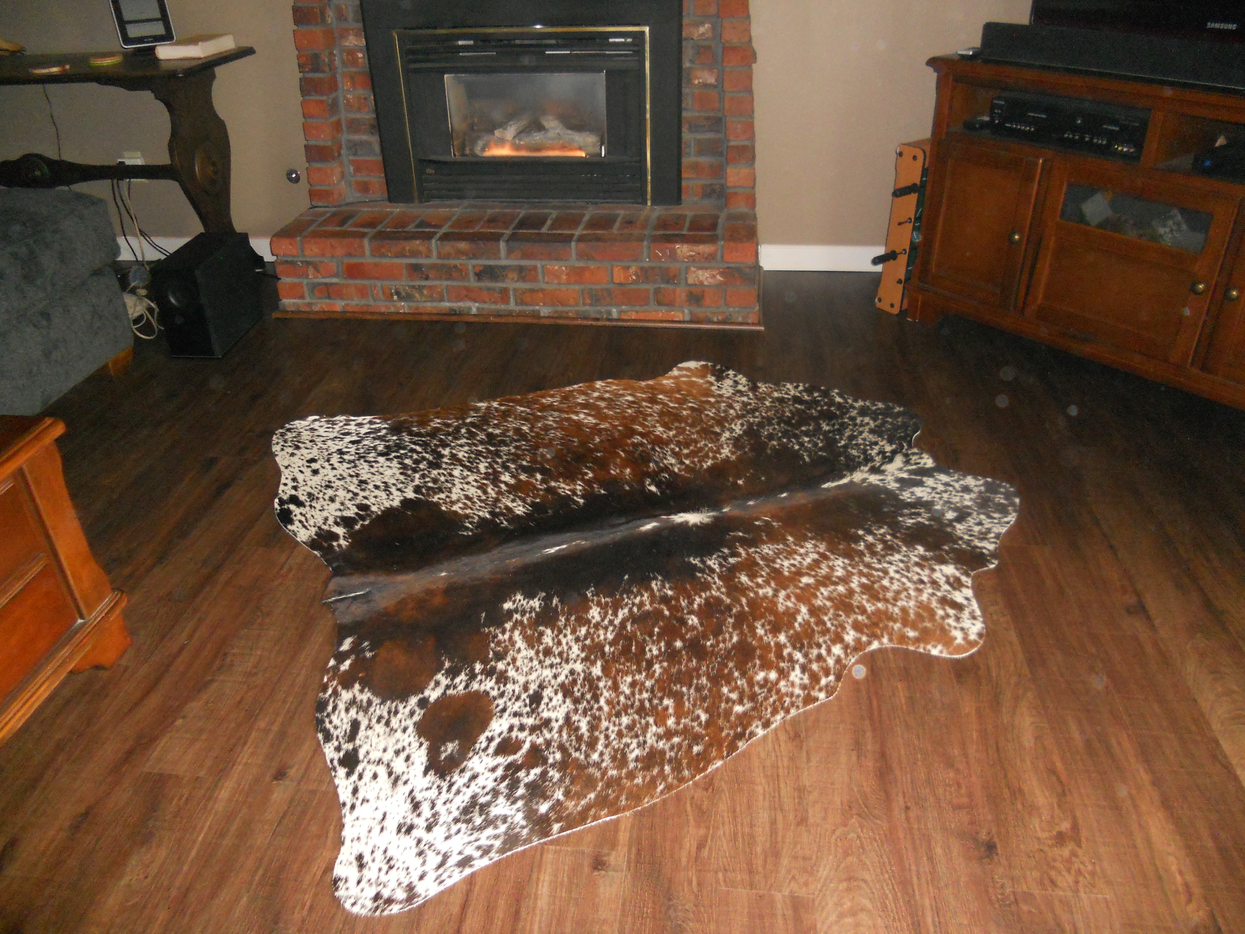 Cowhide rug on wood floor near fireplace